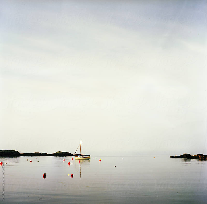 ealing boat in a cove in Wales by Léa Jones for Stocksy United