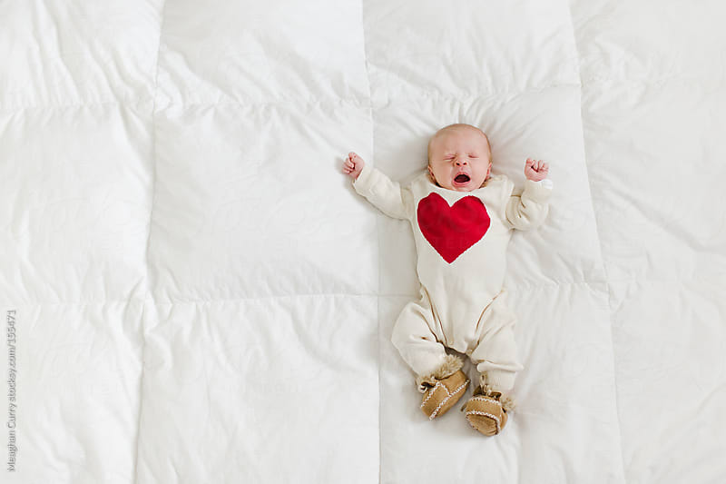 yawning newborn in a heart onesie by Meaghan Curry for Stocksy United