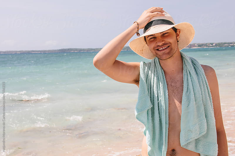 Young hispanic latin tourist on the beach wearing a hat and a towel by Alejandro Moreno de Carlos for Stocksy United