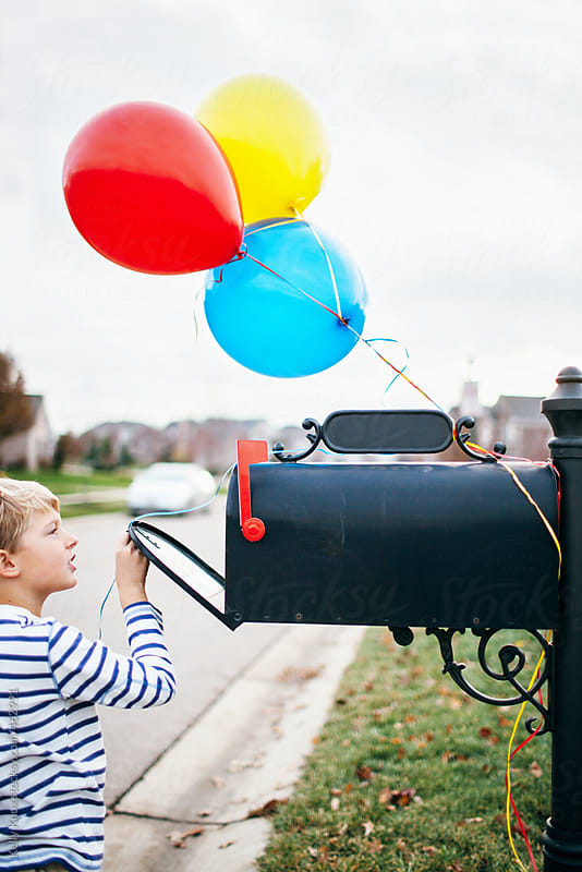 boy opening mailbox decorated with birthday balloons by Kelly Knox for Stocksy United
