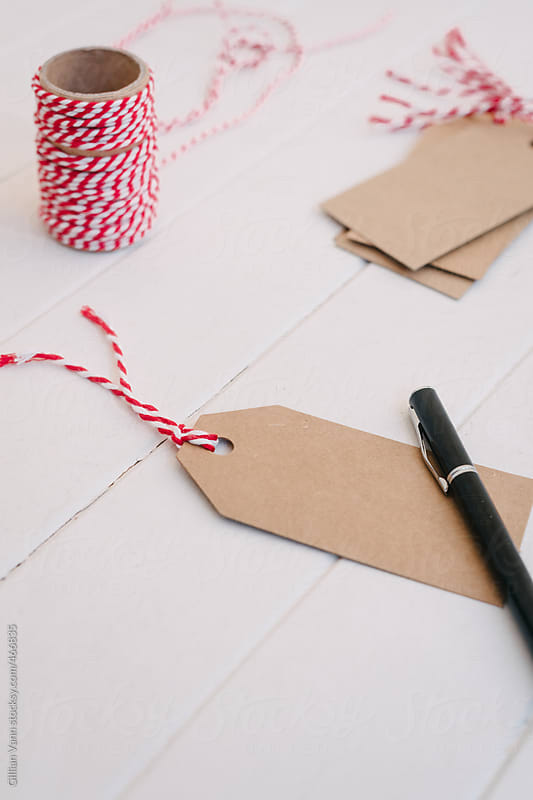 christmas tags in plain cardboard with red string, blank with pen by Gillian Vann for Stocksy United