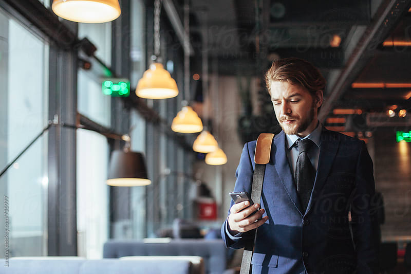 Businessman Texting in a Bar by Lumina for Stocksy United