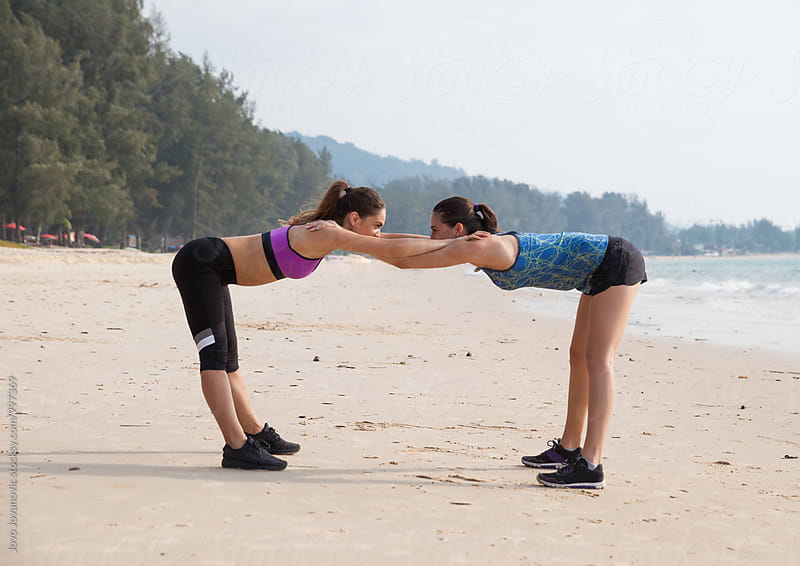 Girlfriends exercising together at the beach by Jovo Jovanovic for Stocksy United