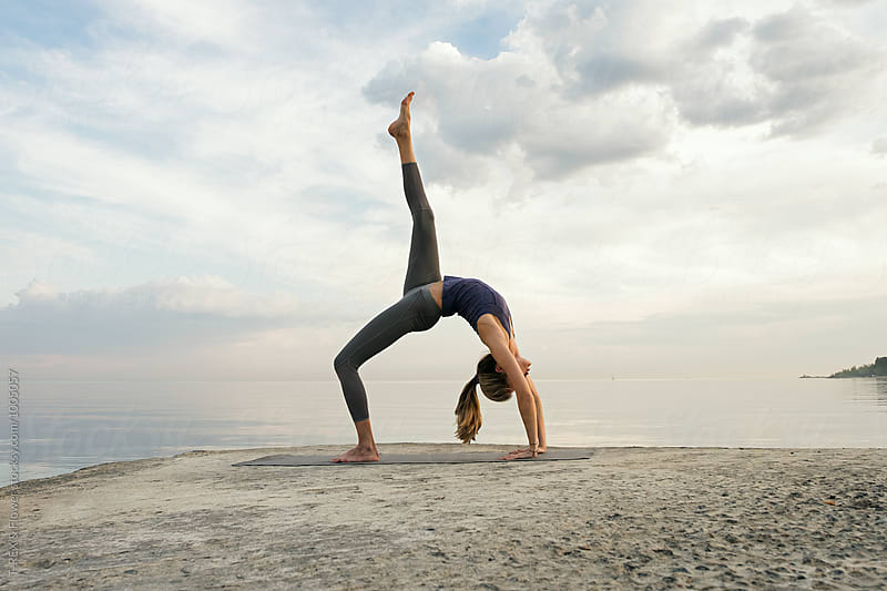 Side view of woman in upward bow pose by Danil Nevsky for Stocksy United