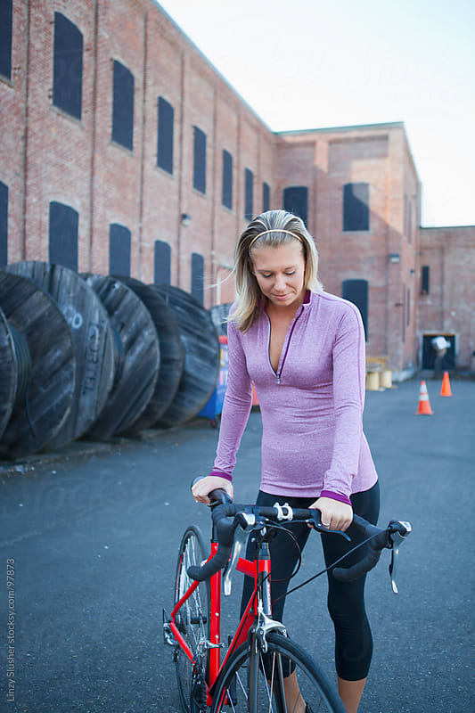 Athletic female resting with bicycle in urban background by Linzy Slusher for Stocksy United