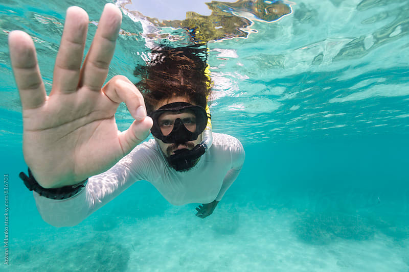 Beautiful young man showing OK sign while snorkeling turqoise tropical waters of Thailand by Jovana Milanko for Stocksy United
