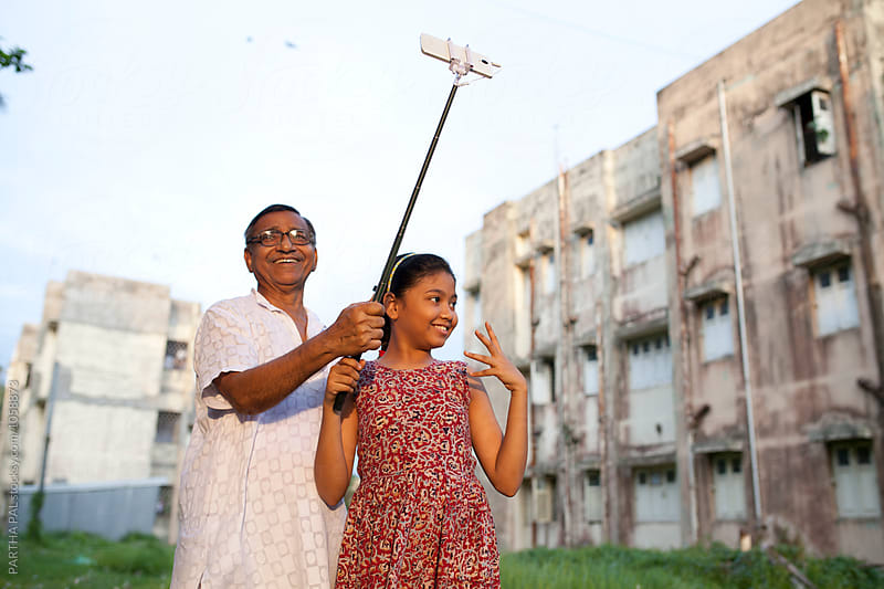 Aged man and grandchild taking selfie with selfie stick by PARTHA PAL for Stocksy United