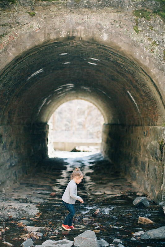 little girl hiking on rocks in front of a tunnel by Meaghan Curry for Stocksy United