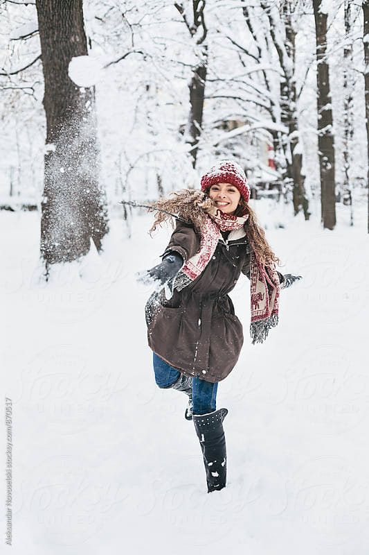 Beautiful young woman throwing snowball towards the camera by Aleksandar Novoselski for Stocksy United