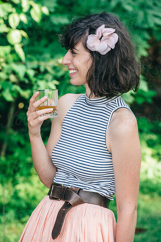 Woman drinking a summer cocktail by Jen Grantham for Stocksy United