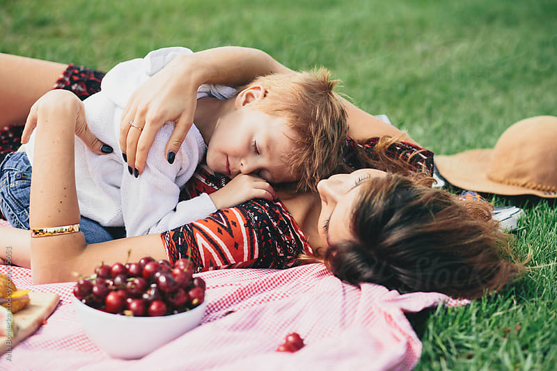 Mother and son napping at a family picnic in the summer by Ania Boniecka for Stocksy United