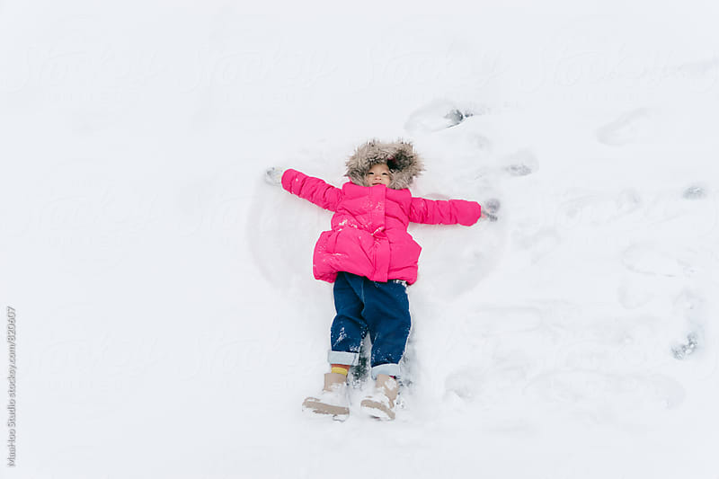 Cute toddler girl making snow angel by Maa Hoo for Stocksy United