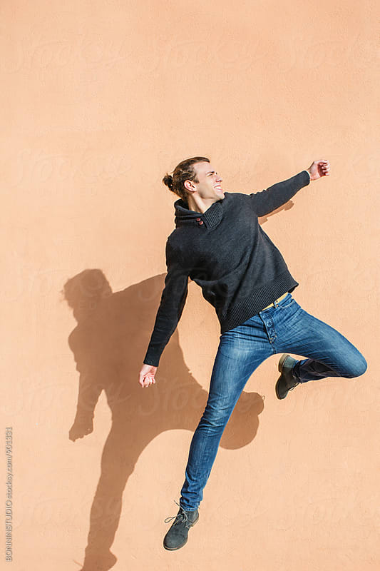 Teenage boy jumping in front of a wall. by BONNINSTUDIO for Stocksy United
