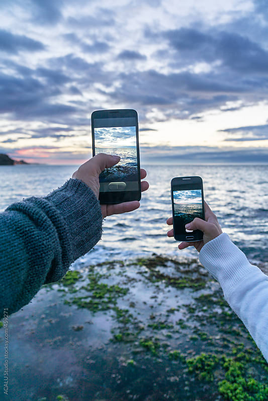 Couple photographing with their smartphone a seascape by ACALU Studio for Stocksy United
