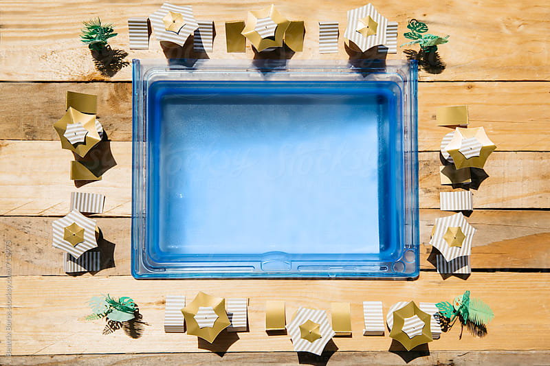 Overhead photo of a swimming pool with umbrellas and beach chairs around it by Beatrix Boros for Stocksy United