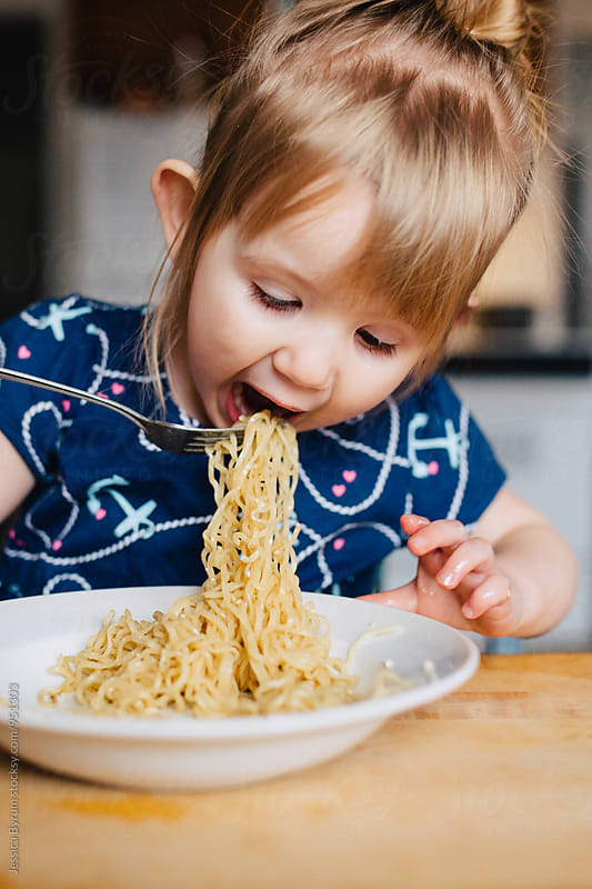Girl eating noodles with fork by Jessica Byrum for Stocksy United