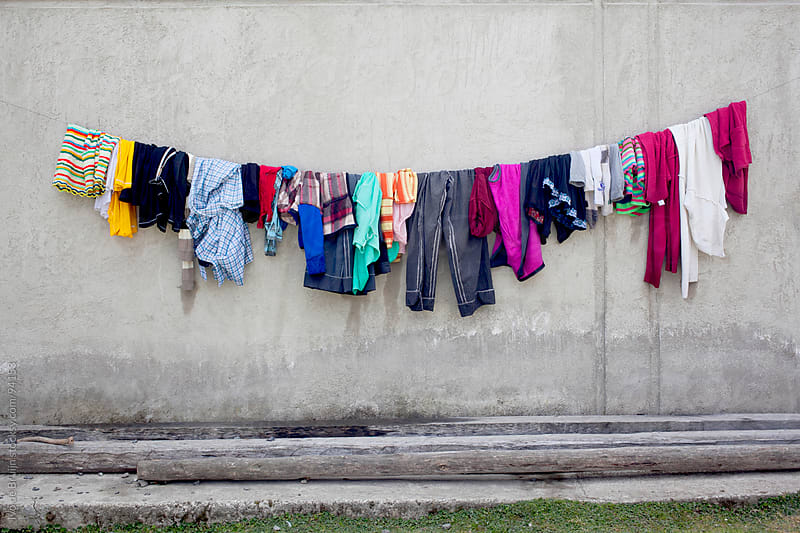 Colourful wet laundry hanging to dry in front of a wall by Ivo de Bruijn for Stocksy United