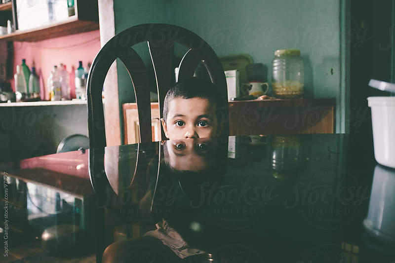 Baby girl sitting at dinning table,peeking at camera by Saptak Ganguly for Stocksy United