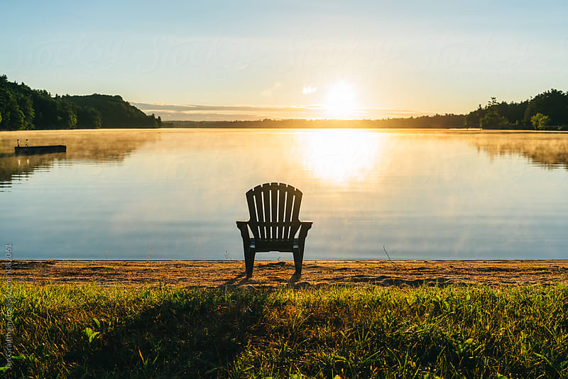Adirondack chair on the beach during sunrise by Jen Grantham for Stocksy United