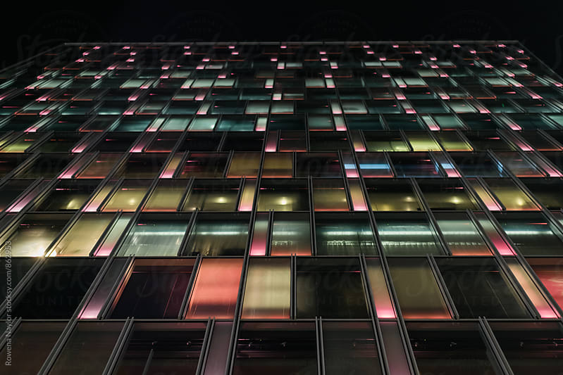 Colorful glass windows on building at night by Rowena Naylor for Stocksy United