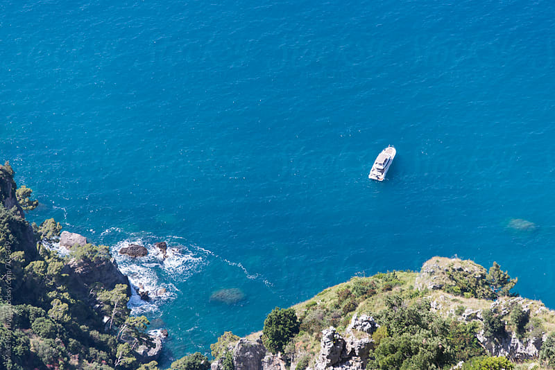 Rocky cliff side with a boat in a bright blue sea by Mike Marlowe for Stocksy United