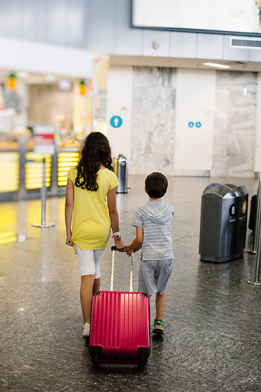 Siblings  walk away pulling together a pink luggage at the airport by Beatrix Boros for Stocksy United