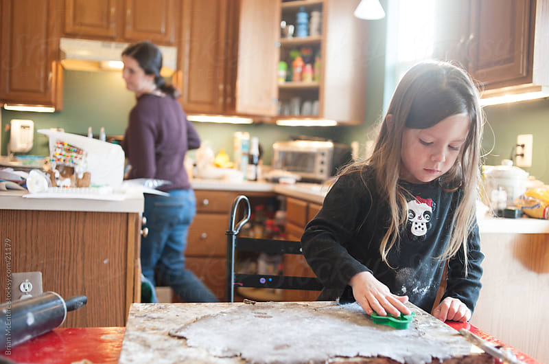 Child Baking: Daughter Helps Mom Bake Gingerbread Cookies by Brian McEntire for Stocksy United