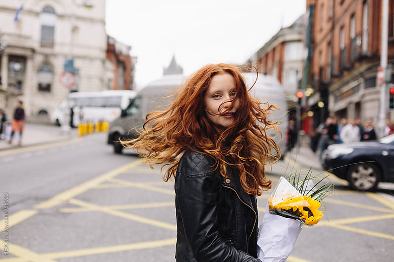 Young Beautiful Girl On the Street Holding Sunflowers by Mattia Pelizzari for Stocksy United