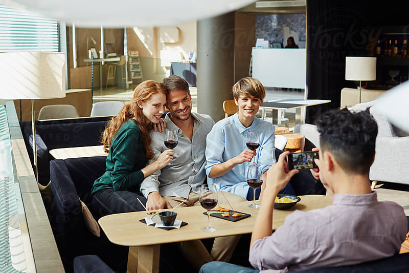 Man Photographing Happy Friends At Restaurant by ALTO IMAGES for Stocksy United
