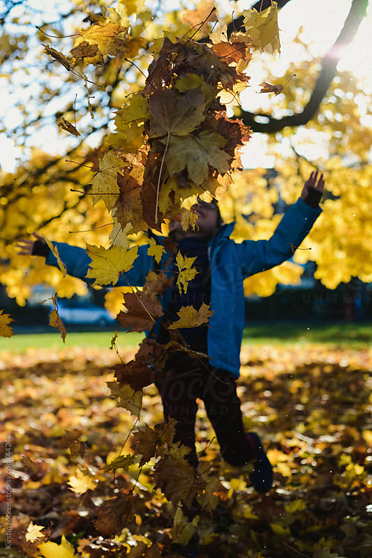 Caucasian boy throwing autumnal leaves by Kirstin Mckee for Stocksy United