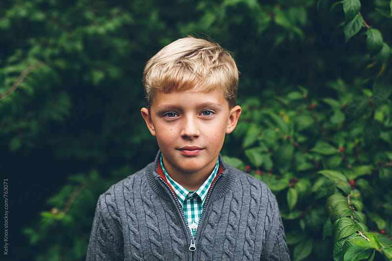 portrait of a serious boy in autumn by Kelly Knox for Stocksy United