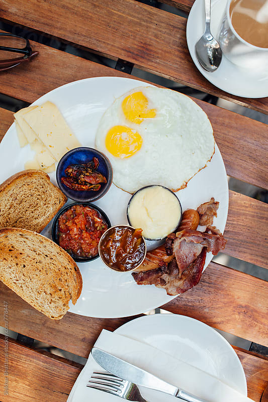A delicious full breakfast plated on a wooden table. by Shikhar Bhattarai for Stocksy United