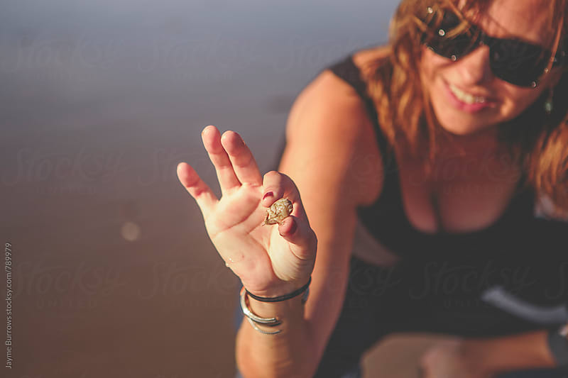 Woman Holding Small Crab by Jayme Burrows for Stocksy United