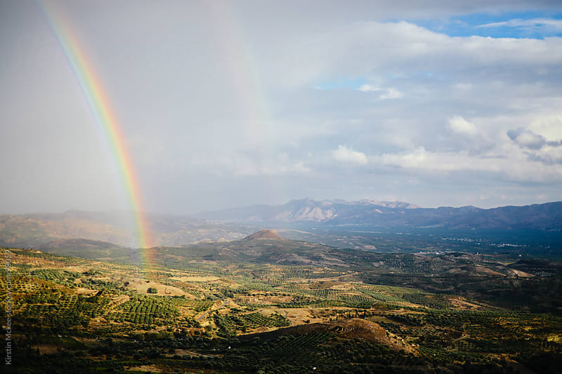 Rainbow across a valley in Crete, Greece.  by Kirstin Mckee for Stocksy United