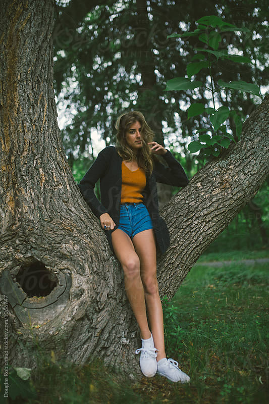Young woman standing next to a tree by Douglas Robichaud for Stocksy United
