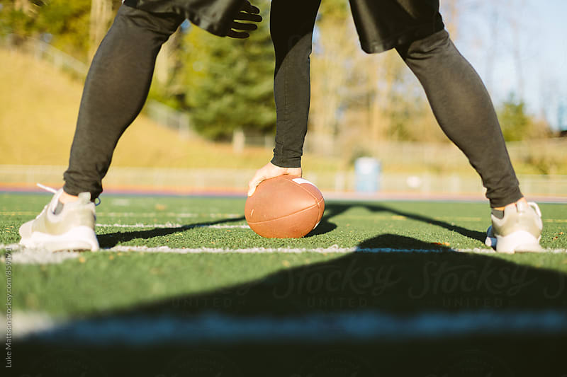 Athletic Man Preparing To Snap Football On Artificial Turf Field by Luke Mattson for Stocksy United
