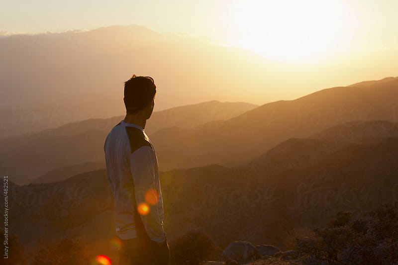 Young man looking out over a sunset from mountain viewpoint by Linzy Slusher for Stocksy United