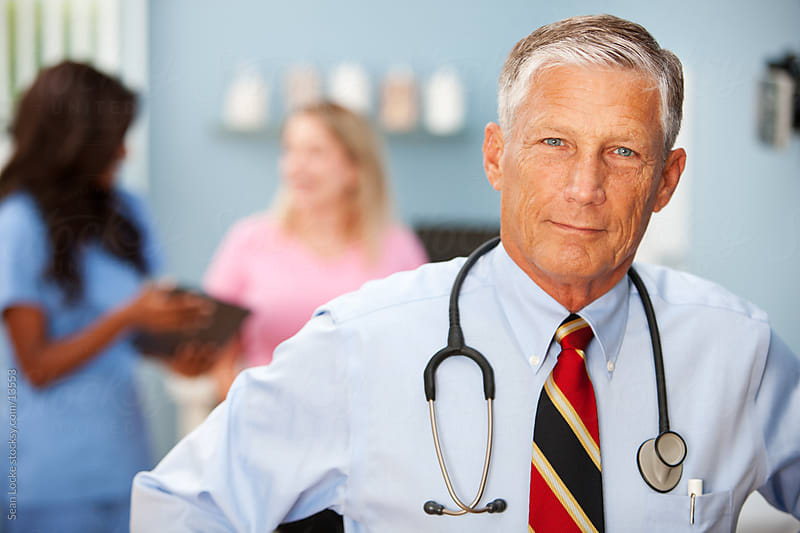 Exam Room: Cheerful Mature Doctor by Sean Locke for Stocksy United
