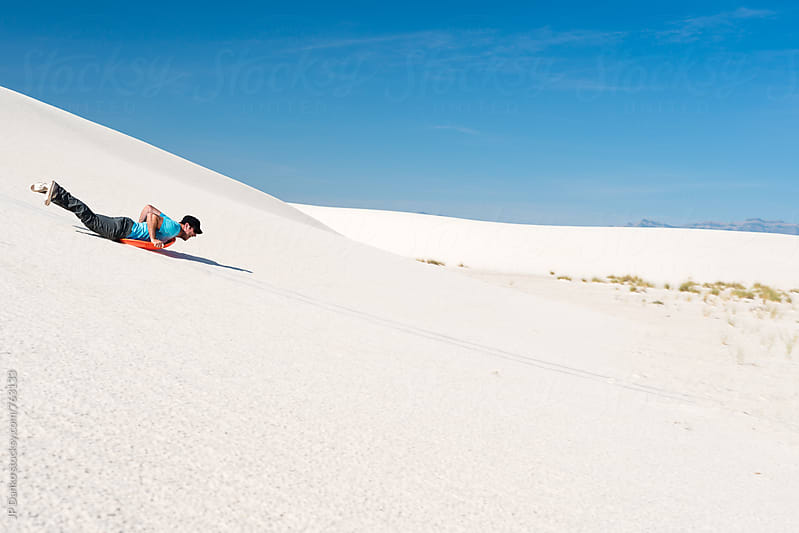 Man Sledding Down Sand Dune Headfirst In White Sands National Monument New Mexico by JP Danko for Stocksy United