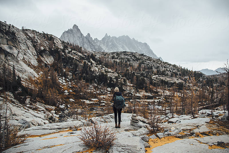 Backpacker against rugged mountainous landscape in Autumn by Tari Gunstone for Stocksy United