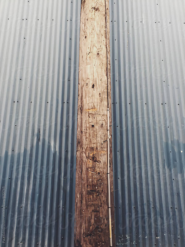 Old telephone pole against metal warehouse wall by Paul Edmondson for Stocksy United