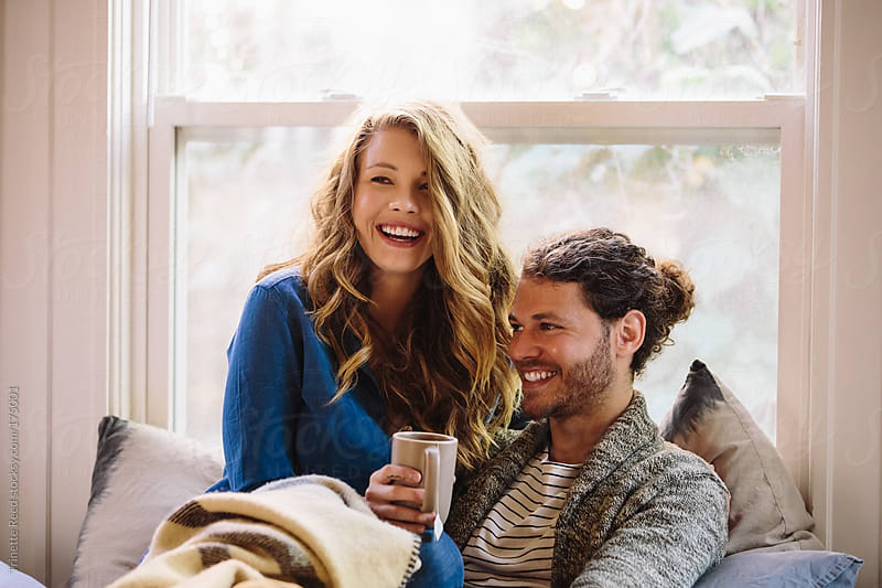 Couple relaxing at home laughing by Trinette Reed for Stocksy United