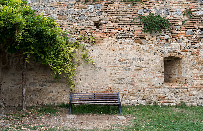Abandoned bench in courtyard against old brick wall by Trent Lanz for Stocksy United