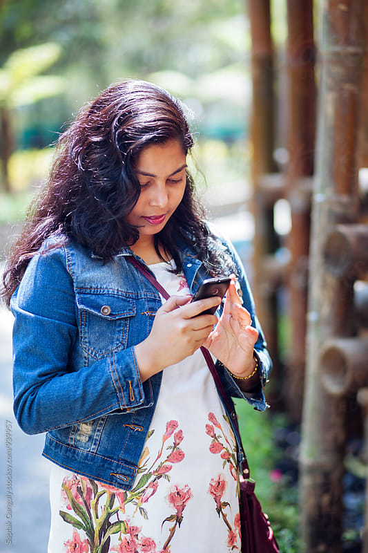 Young woman using mobile phone in the street by Saptak Ganguly for Stocksy United