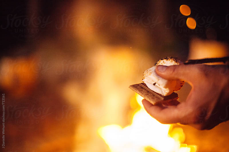 A caucasian hand placing roasted marshmallows on a graham cracker making s'mores. by J Danielle Wehunt for Stocksy United