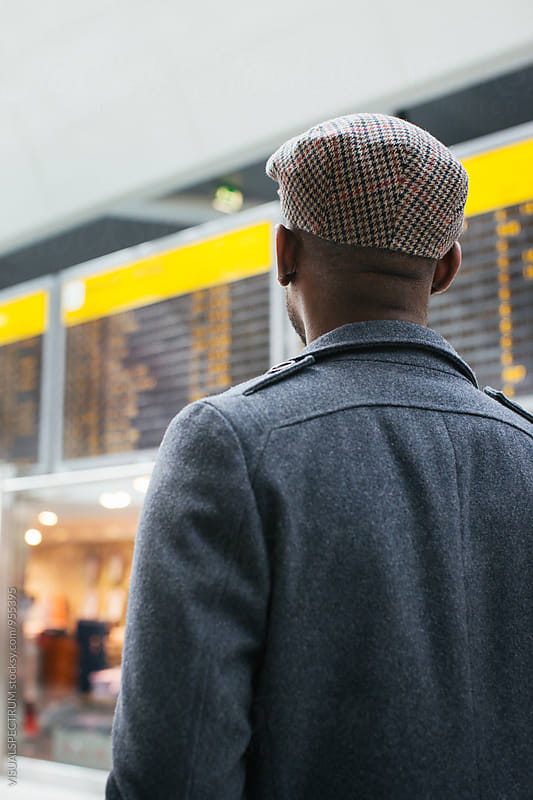 Smartly Dressed Young Black Man Looking at Arrival/Departure Board in Airport by VISUALSPECTRUM for Stocksy United