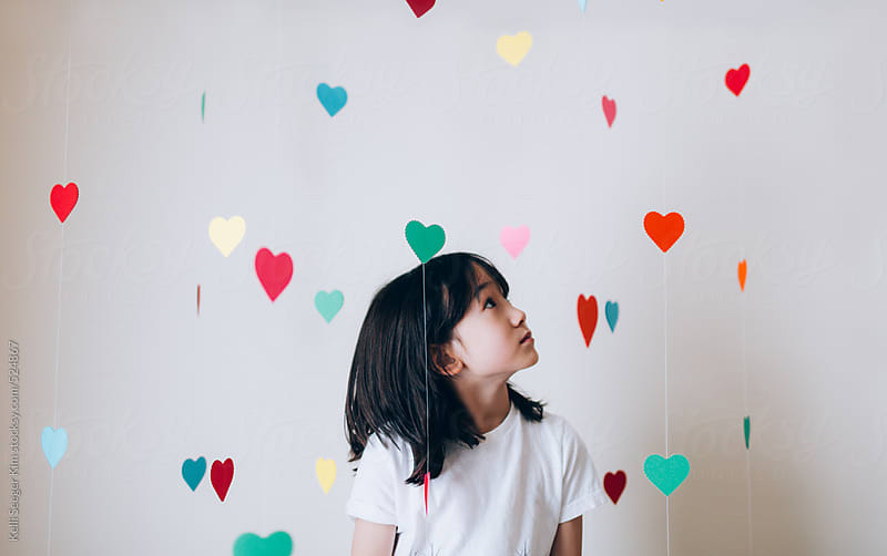 Young boy looks at colorful hearts floating around him by kelli kim for Stocksy United