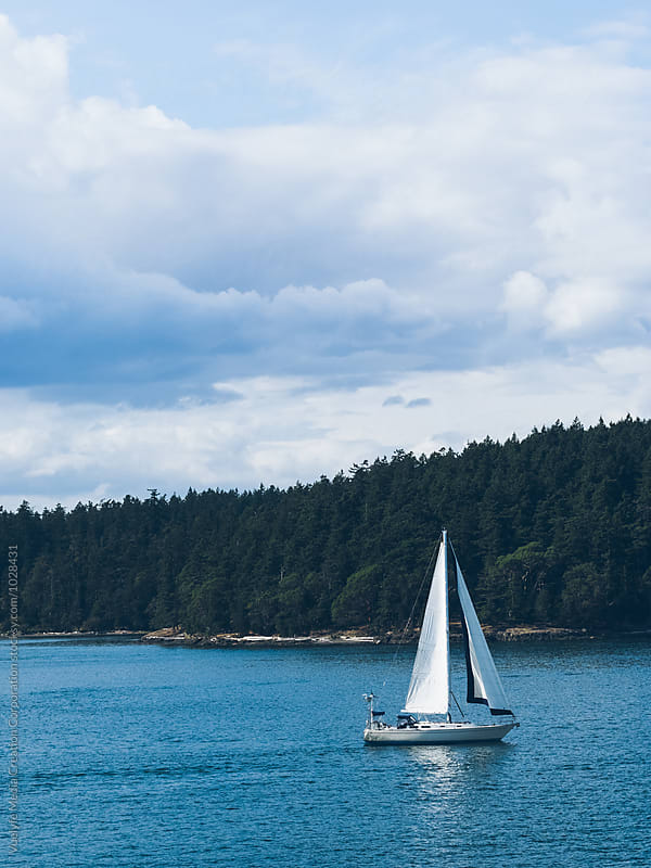 a white silboat crusing on sea against cloudy sky by unite  images for Stocksy United