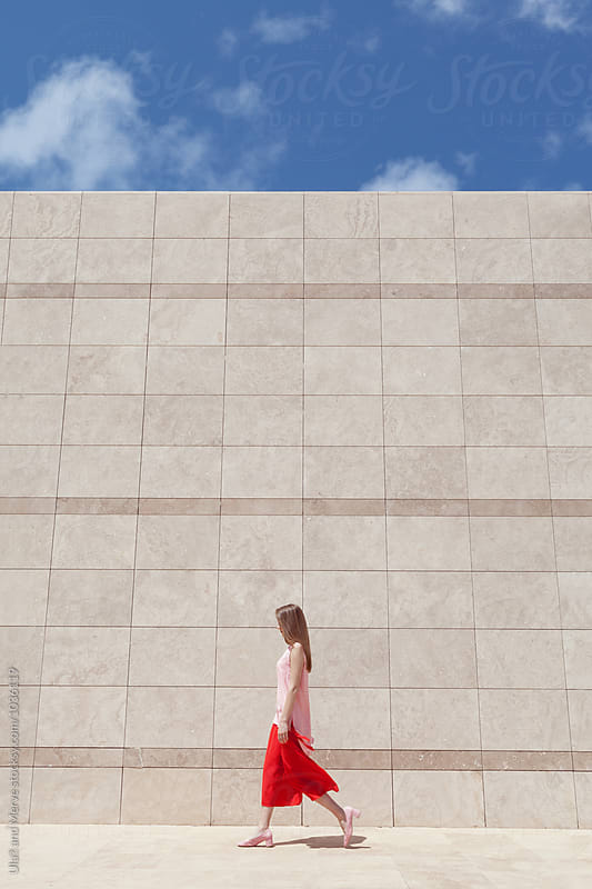blond woman walking in front of a marble wall by Ulaş and Merve for Stocksy United