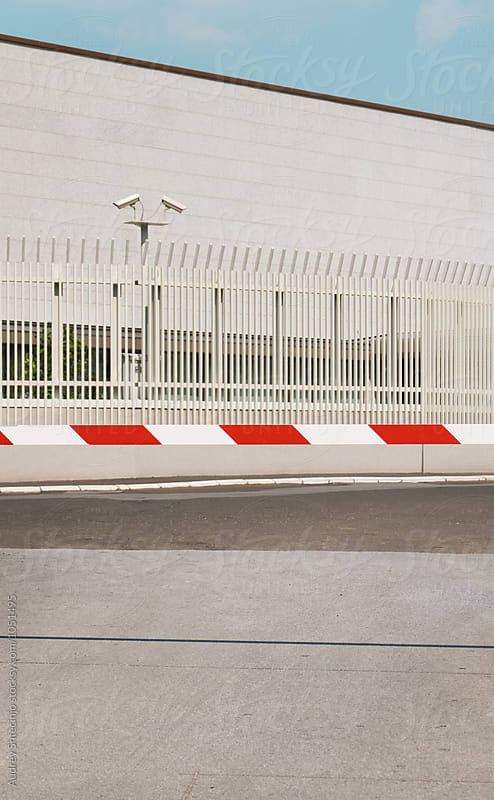 White building with cctv security cameras observing in back of barrier/car stop ramp pulled down. by Marko Milanovic for Stocksy United
